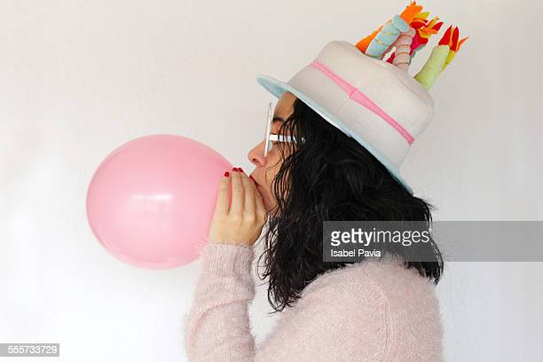 Young woman wearing party hat and blowing balloon