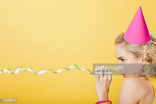 Young woman wearing party hat with party streamer