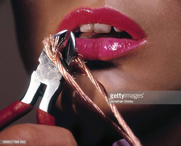 Young woman wearing pink lipstick cutting copper wire close to mouth