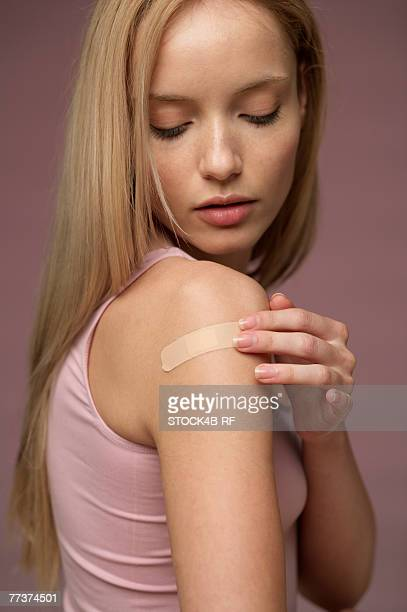 Young woman wearing plaster on upper arm