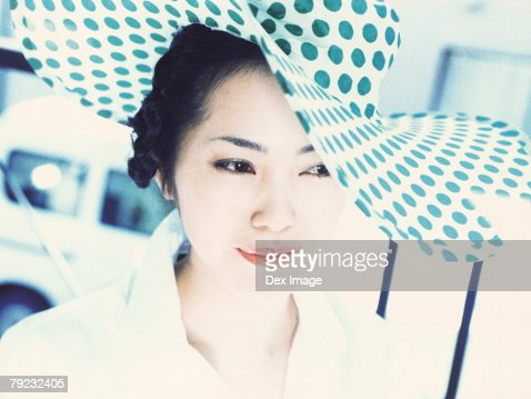 Young woman wearing polka dotted hat, close-up : Stock Photo