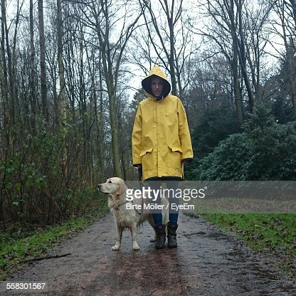 Young Woman Wearing Raincoat Standing With Dog