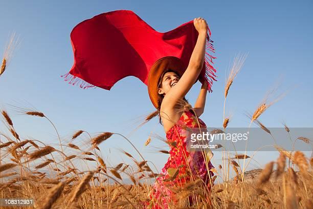 Jeune femme portant robe rouge tenant écharpe rousse dans le vent