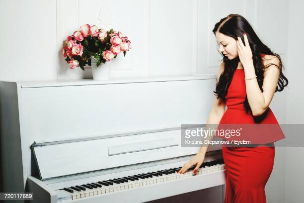 Young Woman Wearing Red Dress Standing By Piano In White Room