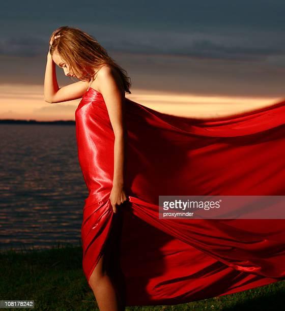Junge Frau mit Rot fließendes Material in der Dämmerung