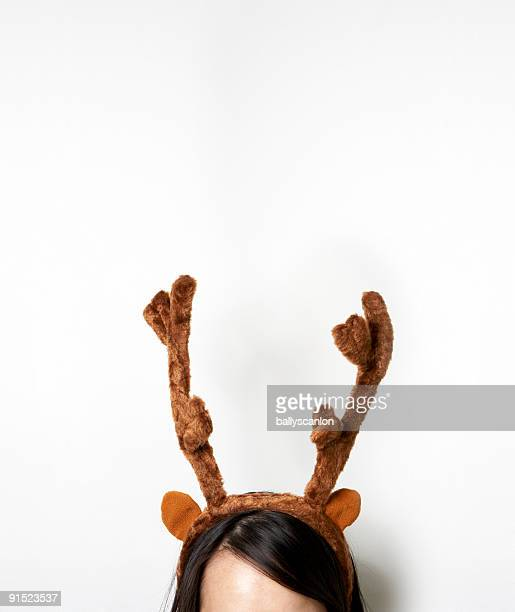 Young woman wearing reindeer antlers, high section