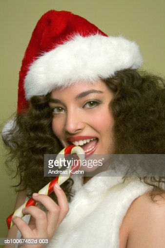 Young woman wearing Santa hat and biting candy cane, portrait, close-up : Stock Photo