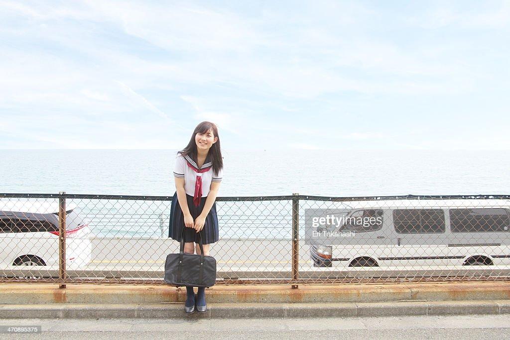 Young woman wearing school uniform, carrying bag