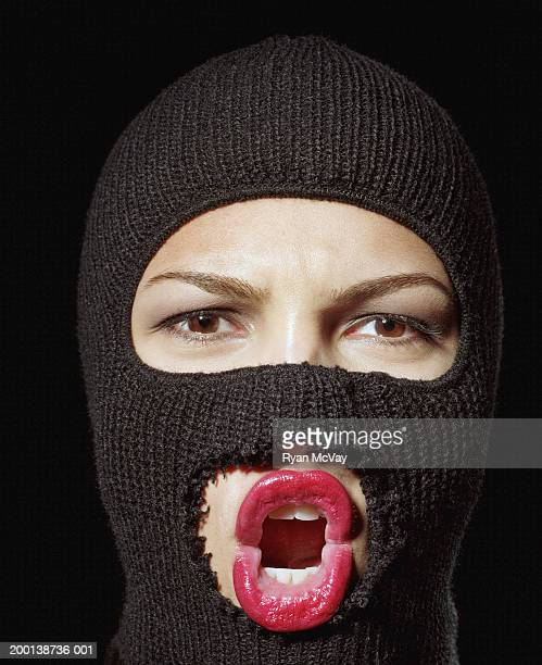 Young woman wearing ski mask, mouth open, close-up