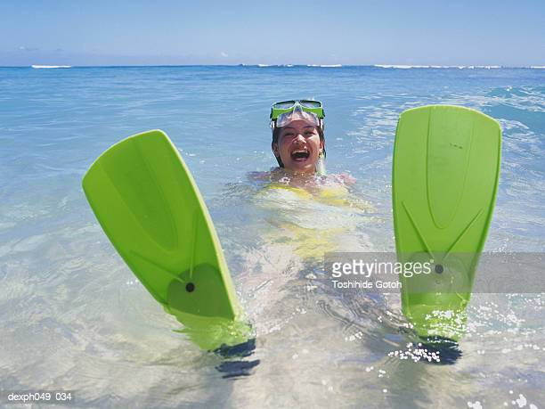 Young woman wearing snorkels and flippers, sitting in shallows