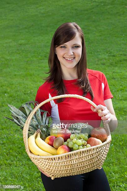 Young woman wearing sports clothing, smiling and holding a basket of fruit