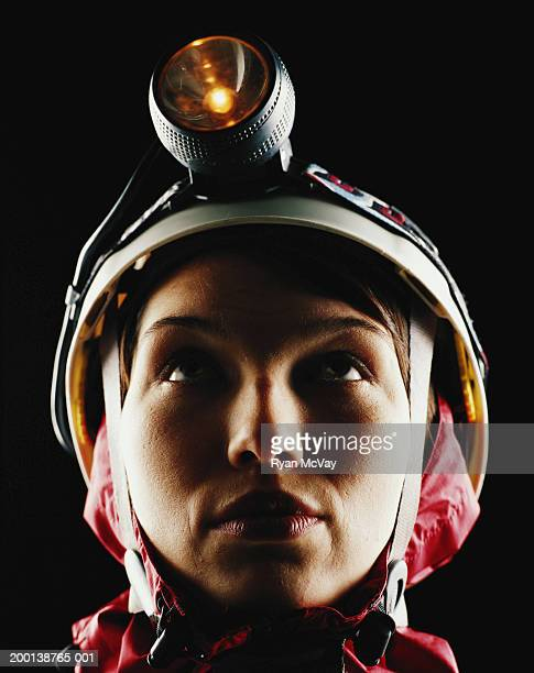 Young woman wearing sports helmet and headlamp, looking up