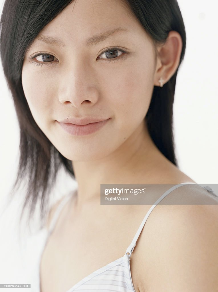Young woman wearing striped vest, smiling, close-up, portrait : Stock Photo