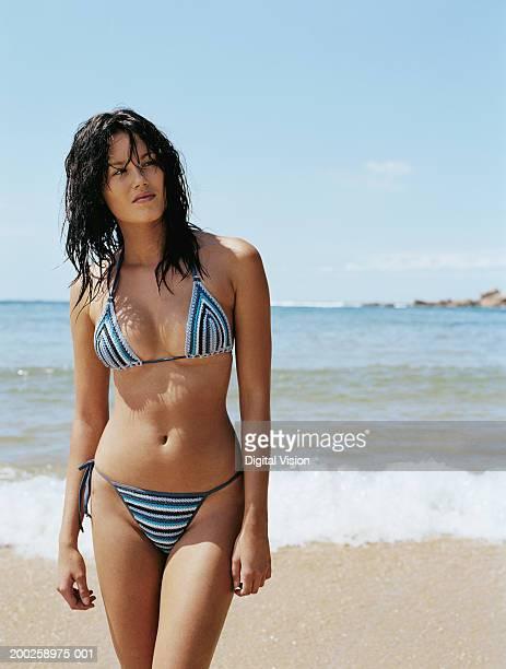 Young woman wearing stripey bikini, standing on beach