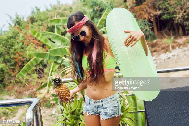 Young woman wearing summer clothes, holding pineapple and inflatable ring