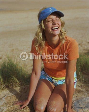 905b5e77 Young woman wearing sun visor, kneeling on sand dune, squinting : Stock  Photo