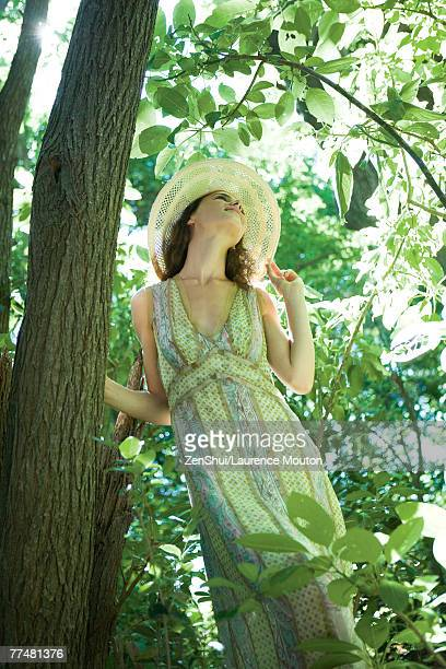 Young woman wearing sundress and sun hat, standing next to tree, low angle view
