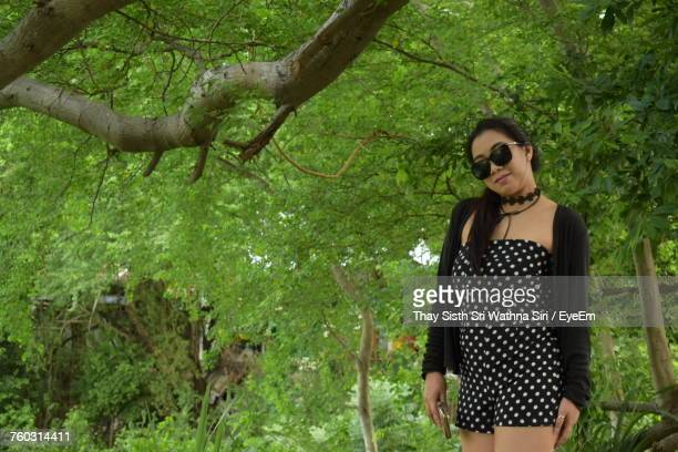 Young Woman Wearing Sunglasses Against Trees