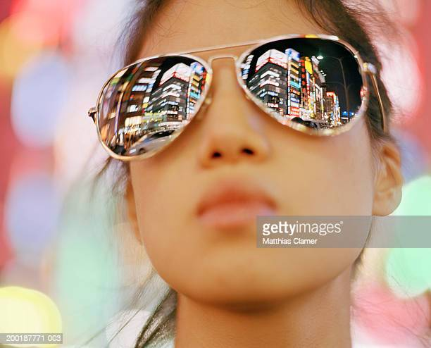 Young woman wearing sunglasses, close-up signage reflected in glasses