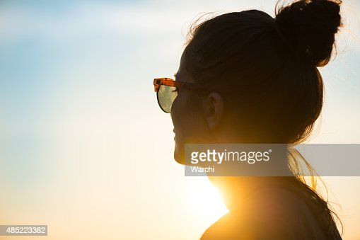 Young woman  wearing sunglasses looking at sunset
