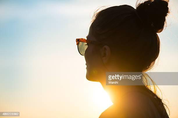 Jovem mulher vestindo Óculos de sol, olhando ao pôr do sol