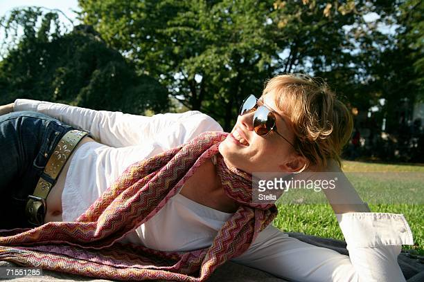 A young woman wearing sunglasses lying in a park