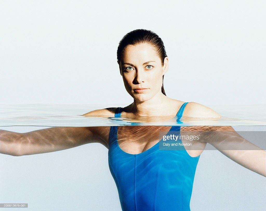 Young woman wearing swimsuit, head and shoulders above water, portrait : Stock Photo