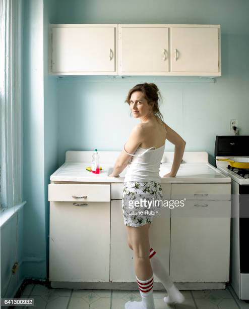 Young woman wearing tee shirt in a blue vintage kitchen