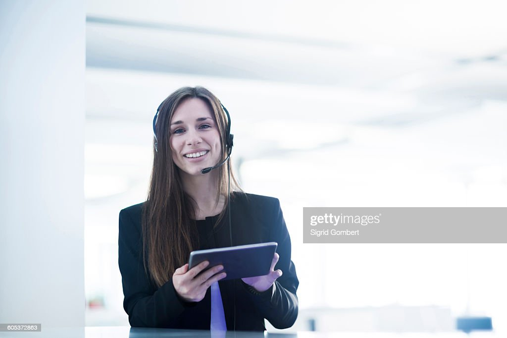 Young woman wearing telephone headset holding digital tablet looking at camera smiling