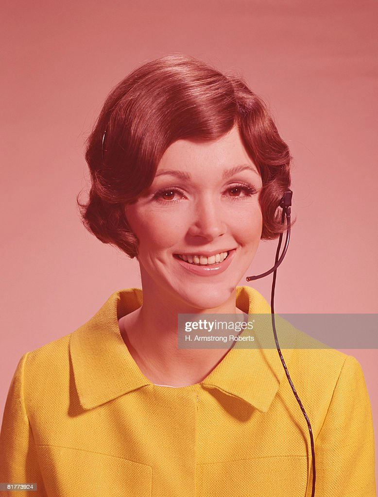 Young woman wearing telephone headset, smiling. (Photo by H. Armstrong Roberts/Retrofile/Getty Images) : Stock Photo