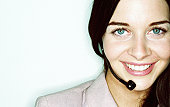 Young woman wearing telephone headset, smiling, portrait, close-up