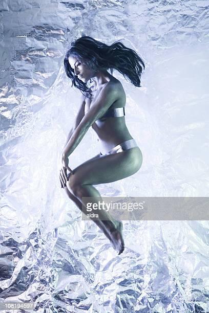 Junge Frau mit Tin Metallic Bikini-Jumping in Air