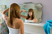 Young woman wearing towel cutting fringe in mirror, rear view