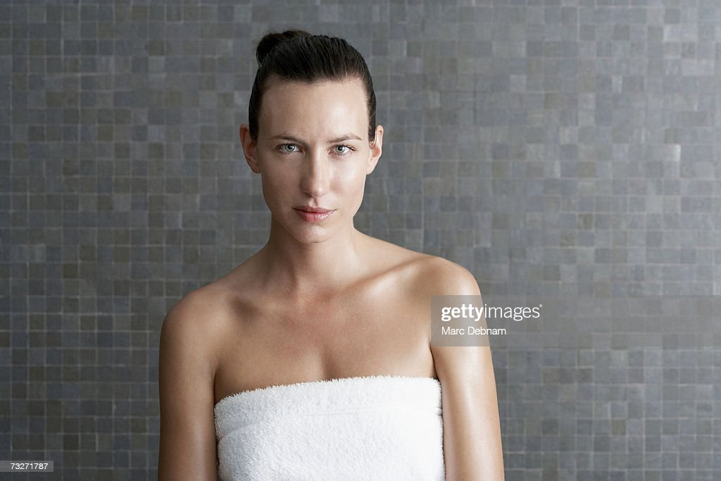 Young woman wearing towel in bathroom, portrait : Stock Photo