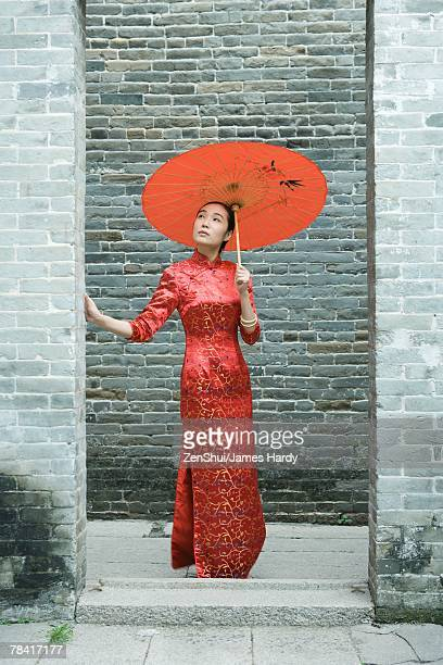 Young woman wearing traditional Chinese clothing, standing with parasol, full length