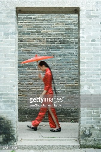 Young woman wearing traditional Chinese clothing, walking with parasol, side view, blurred motion