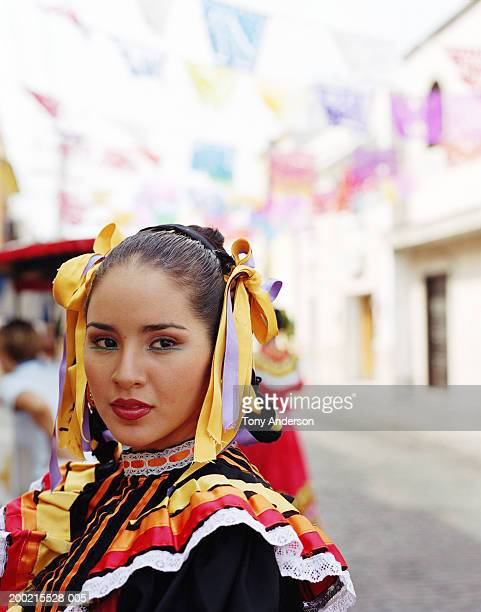 Young woman wearing traditional dress at fiesta, close-up, portrait