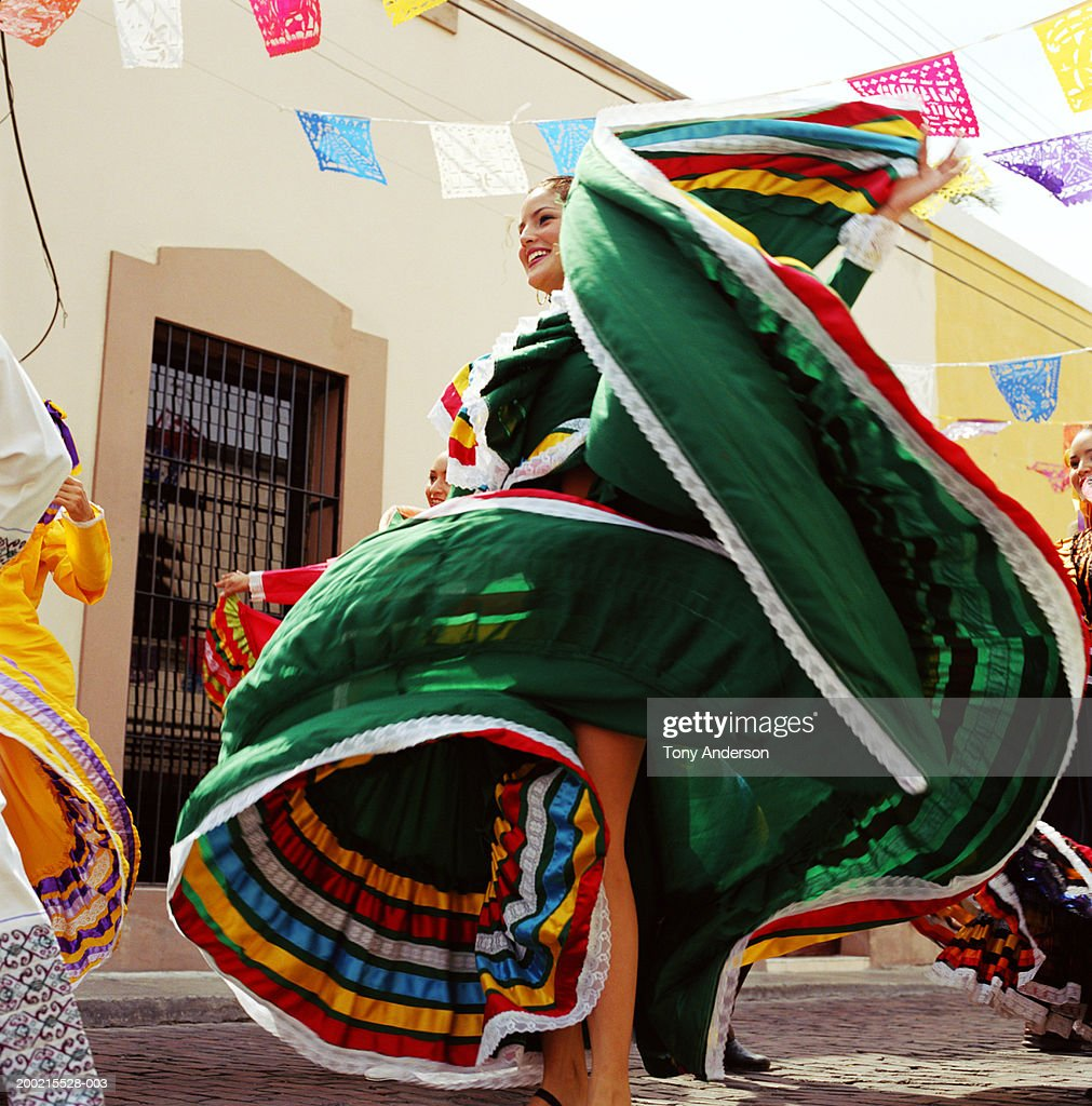 Young woman wearing traditional dress, dancing at fiesta : Stock Photo