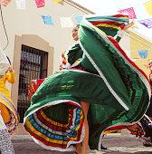 Young woman wearing traditional dress, dancing at fiesta