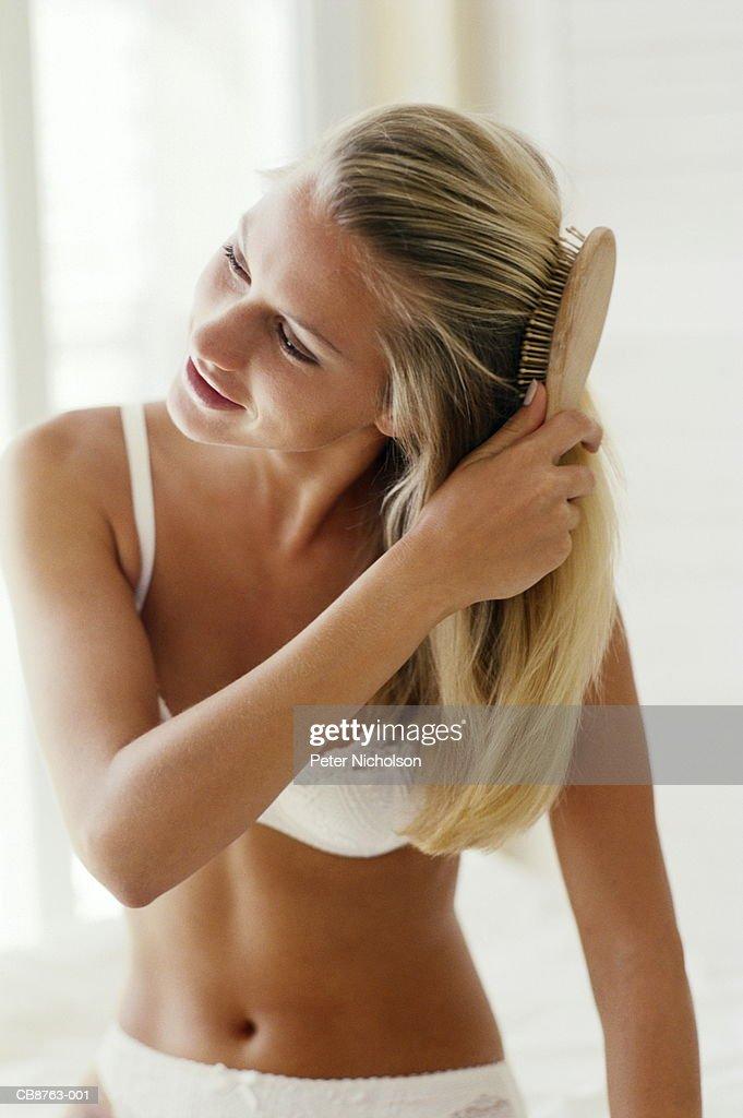 Young woman wearing underwear, brushing hair
