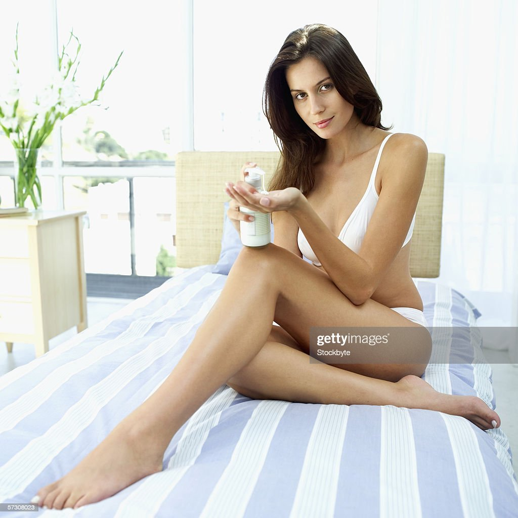 Young woman wearing underwear sitting on a bed pouring moisturizing lotion into her hands : Stock Photo