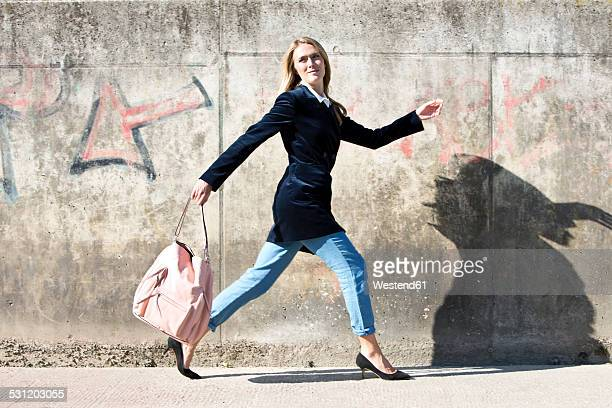 Young woman wearing velvet blazer running in front of a wall