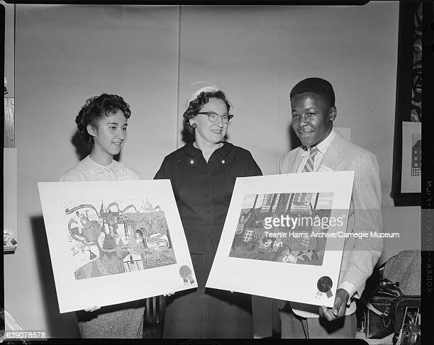Young woman wearing 'Virginia Pokora' name tag and holding painting with prize ribbon woman wearing dark suit and eyeglasses and young man wearing...