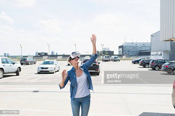young woman wearing VR Glasses at car park