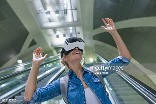 young woman wearing VR Glasses at undergound station