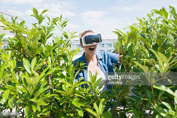 young woman wearing VR Glasses exploring plants