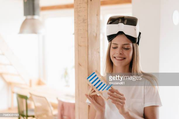 Young woman wearing VR goggles, planning vacation, holding toy chair