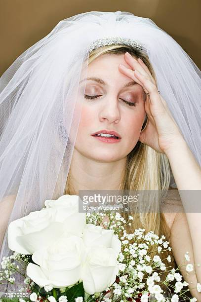 Young woman wearing wedding veil, hand on forehead
