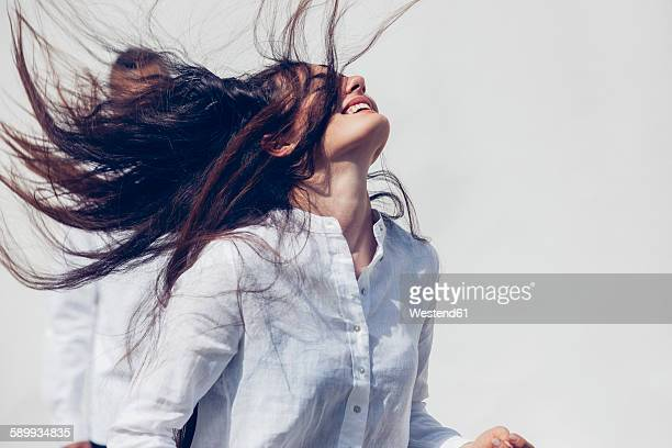 Young woman wearing white blouse tossing her long dark hair in front of white background