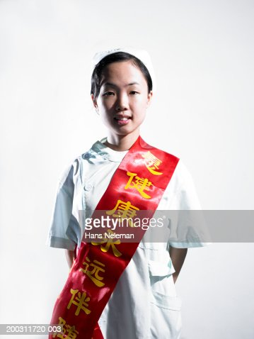 Young woman wearing winner's sash over traditional costume, portrait : Stock Photo
